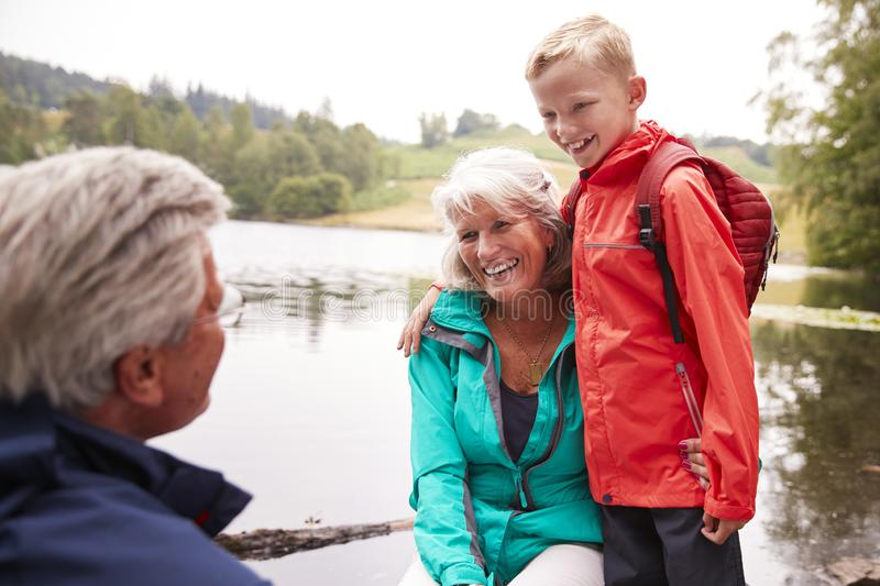 Pre-teen boy standing beside his grandparents, sitting on the shore of a lake, Lake District, UK stock image