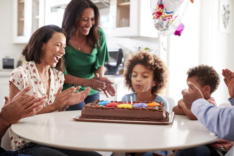 Pre teen girl blowing out the candles on birthday cake sitting at table in the kitchen with her three generation family, selective royalty free stock photos