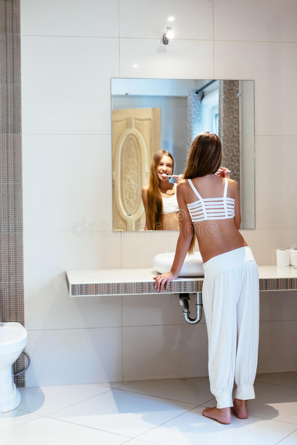 Pre teen girl in the hotel bathroom. Pre teen girl brushes her teeth in the hotel bathroom interior. 10 years old child washing in the morning, lifestyle photo royalty free stock image