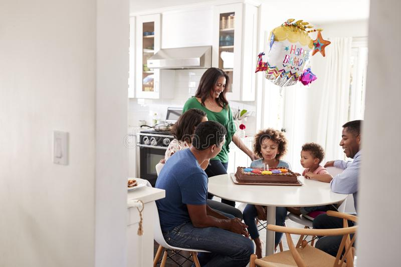Pre teen girl sitting at the kitchen table with her three generation family celebrating her birthday, blowing out candles on her b stock photo