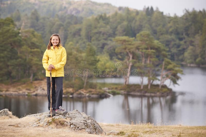 A pre-teen girl standing on a rock holding a stick, smiling to camera, lakeside background stock photography
