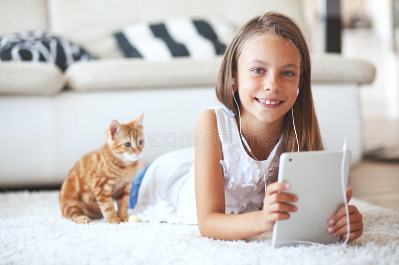 Pre teen girl with tablet pc. Pre teen girl playing on tablet pc laying down on a white carpet at home royalty free stock photos