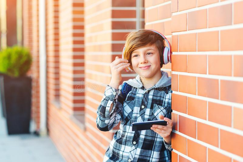 Pre-teenage boy with headphones and mobile phone listening to music at city street. Fashion boy hairstyle. Popular lifestyle music. Play list. Fashion kid urban royalty free stock images