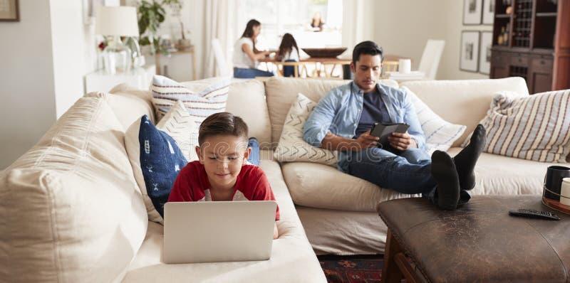 Pre-tienerjongen die op bank die laptop, papazitting met tablet, mum en zuster met behulp van in de achtergrond liggen stock afbeeldingen