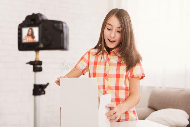 Pre-tienermeisje het openen doos en het hijgen in verrassing stock fotografie