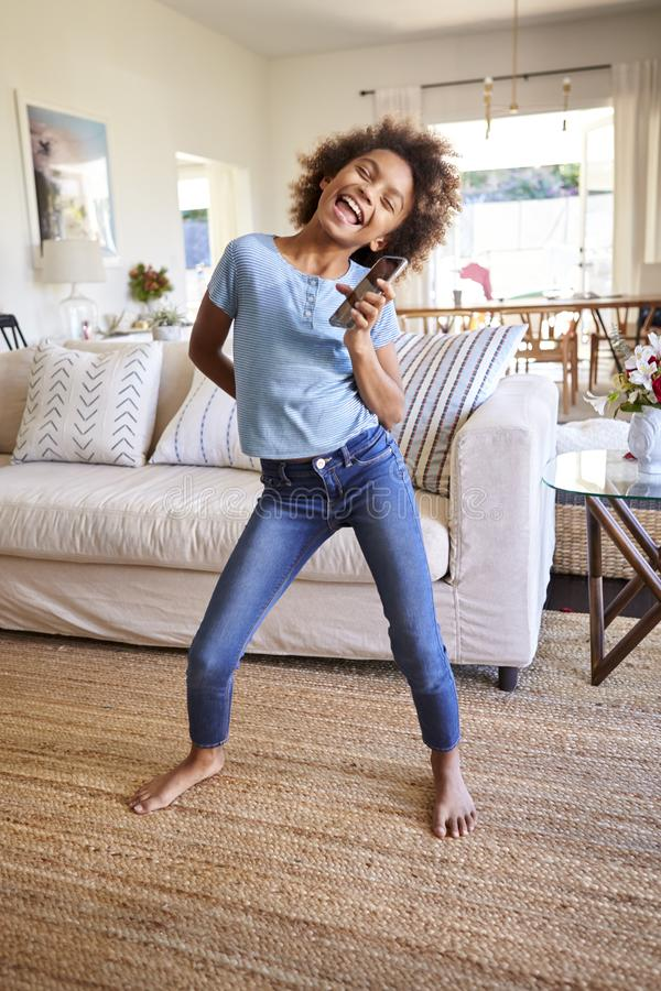 Pre-tonårig afrikansk amerikanflicka som sjunger och dansar i vardagsrummet, genom att använda en social massmediaapp på hennes s royaltyfria foton
