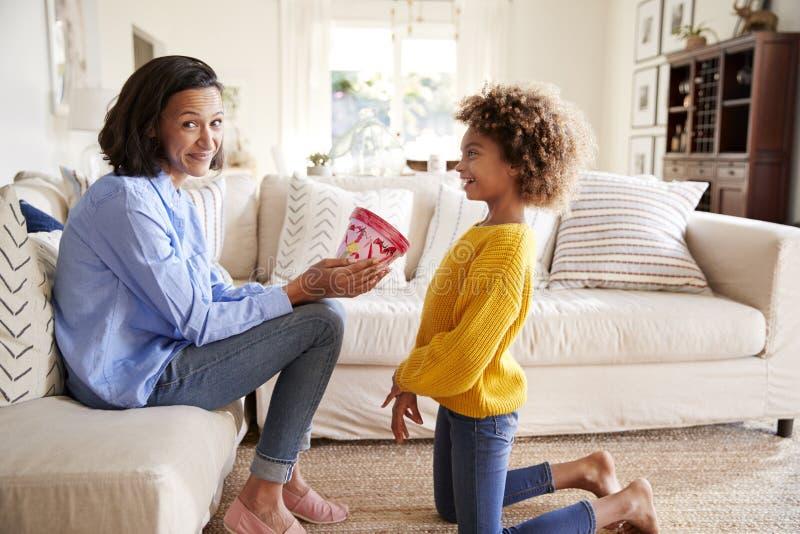 Pre-tonårig flicka som knäfaller och ger hennes moder en hemlagad dekorerad växtkruka, mum som ser till kameran, sidosikt royaltyfria foton