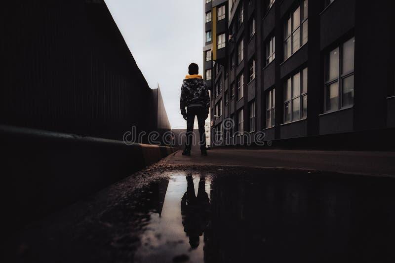 Pre-tonårig pojke på en gata i en storstad bredvid ett höghus bara arkivfoton
