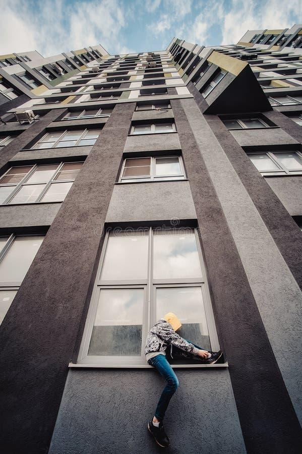 Pre-tonårig pojke på en gata i en storstad bredvid ett höghus bara royaltyfria foton