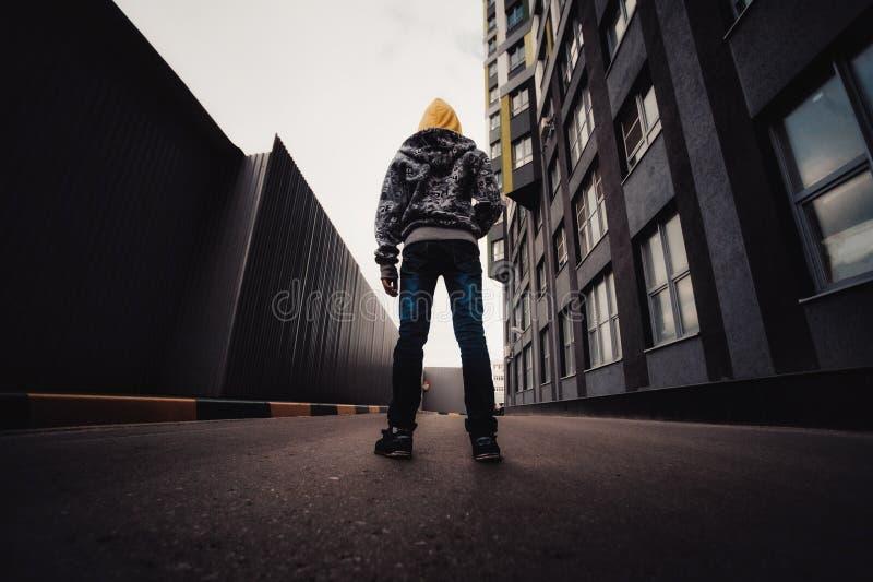 Pre-tonårig pojke på en gata i en storstad bredvid ett höghus bara royaltyfria bilder