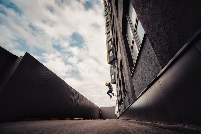 Pre-tonårig pojke på en gata i en storstad bredvid ett höghus bara royaltyfri foto