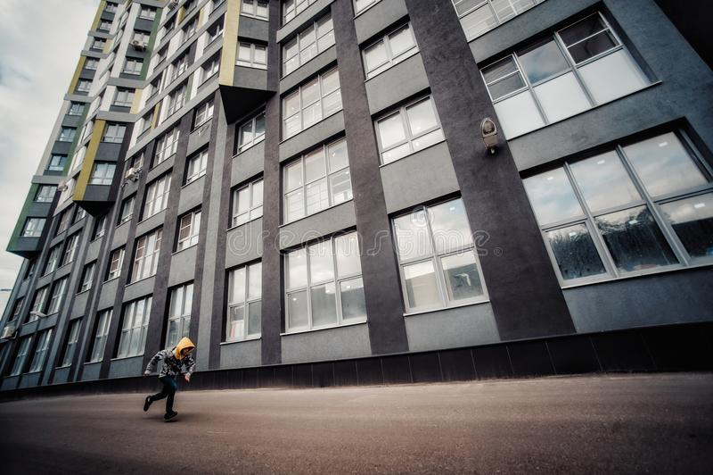 Pre-tonårig pojke på en gata i en storstad bredvid ett höghus bara royaltyfri fotografi