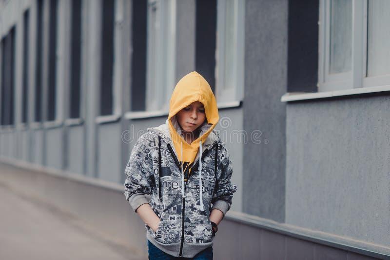 Pre-tonårig pojke på en gata i en storstad bredvid ett höghus bara fotografering för bildbyråer