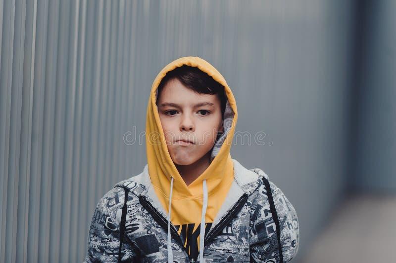 Pre-tonårig pojke på en gata i en storstad bredvid ett höghus bara arkivfoto