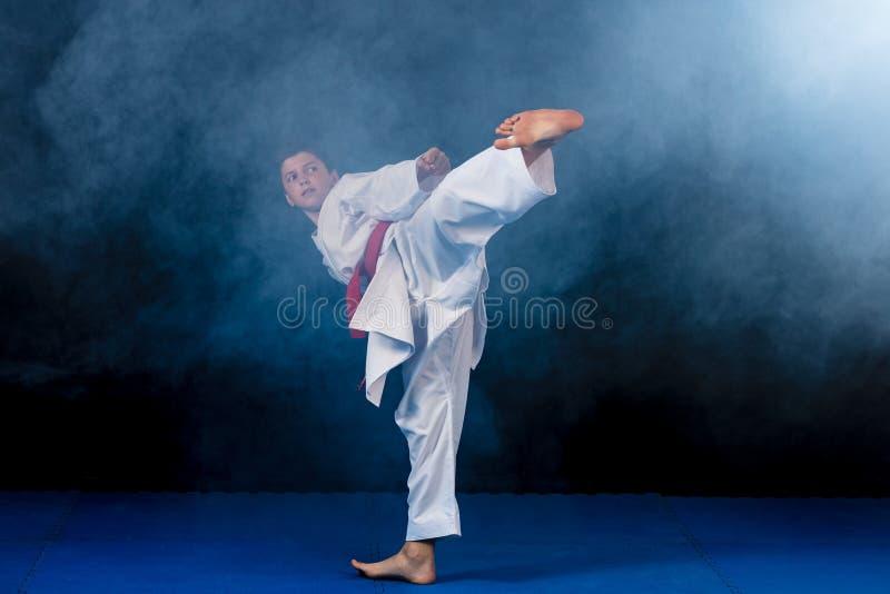 Pre-tonårig pojke som gör karate på en svart bakgrund med rök arkivfoton