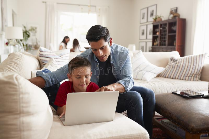 Pre-tonårig pojke som ligger på soffan genom att använda bärbara datorn, farsan som sitter bredvid honom, mumen och systern i bak royaltyfri bild
