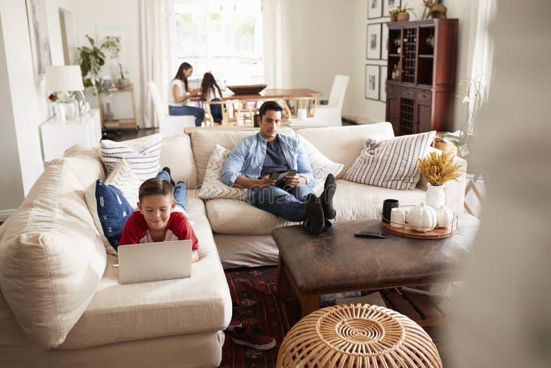 Pre-tonårig pojke som ligger på soffan genom att använda bärbara datorn, farsan som sitter med en minnestavla, mumen och systern  royaltyfria bilder