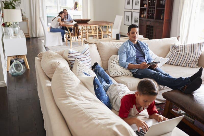 Pre-tonårig pojke som ligger på soffan genom att använda bärbara datorn, farsan som sitter med minnestavlan, mumen och mormodern  arkivfoto