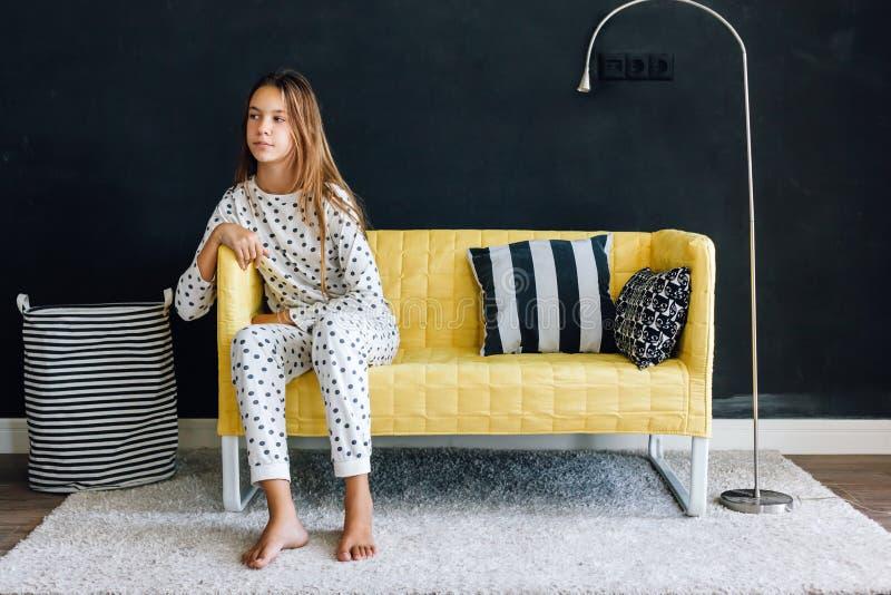 Pre tonårigt barn på soffan mot den svarta väggen i modern uppehälle royaltyfri fotografi