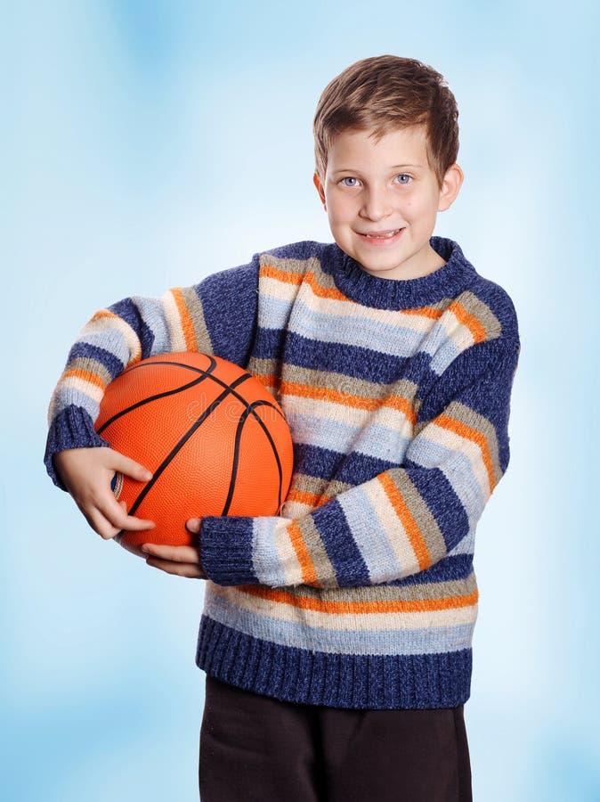 Pre-tonårigt barn som ler barnet med basket arkivbilder