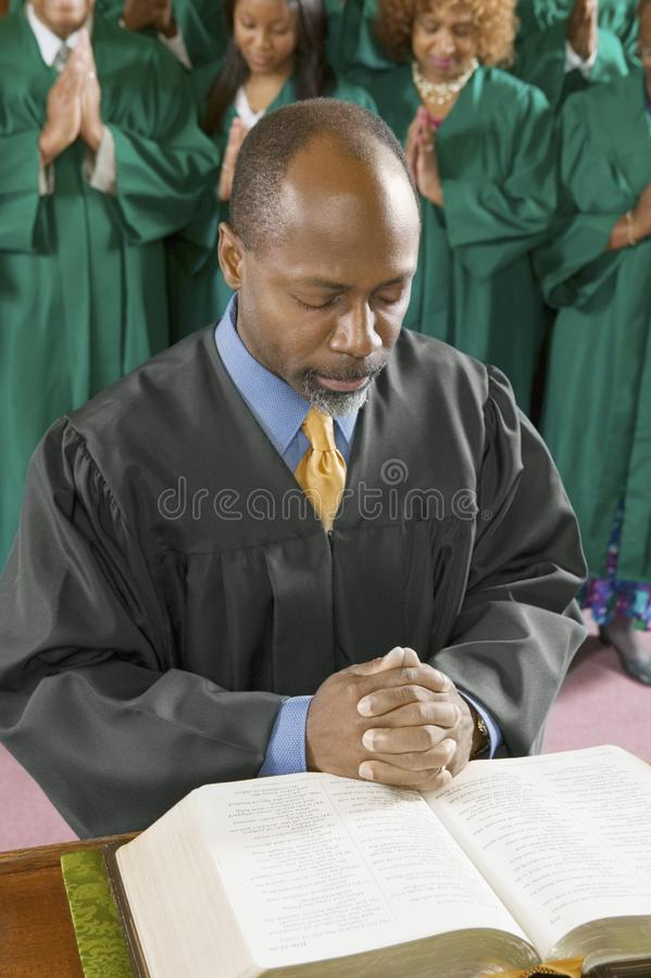 Preacher by altar in church Bowing Head in Prayer. High angle view stock photos