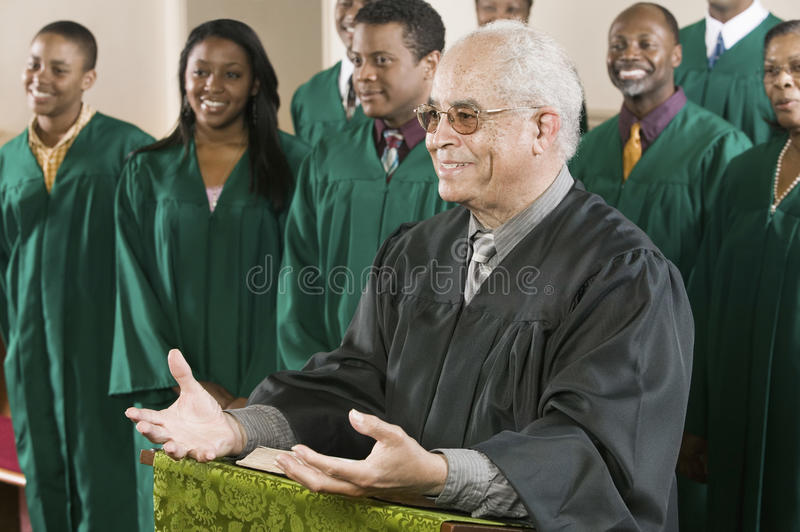 Preacher Standing At Pulpit With Choir In Background At Church. Senior preacher standing at pulpit with choir in background at church royalty free stock images