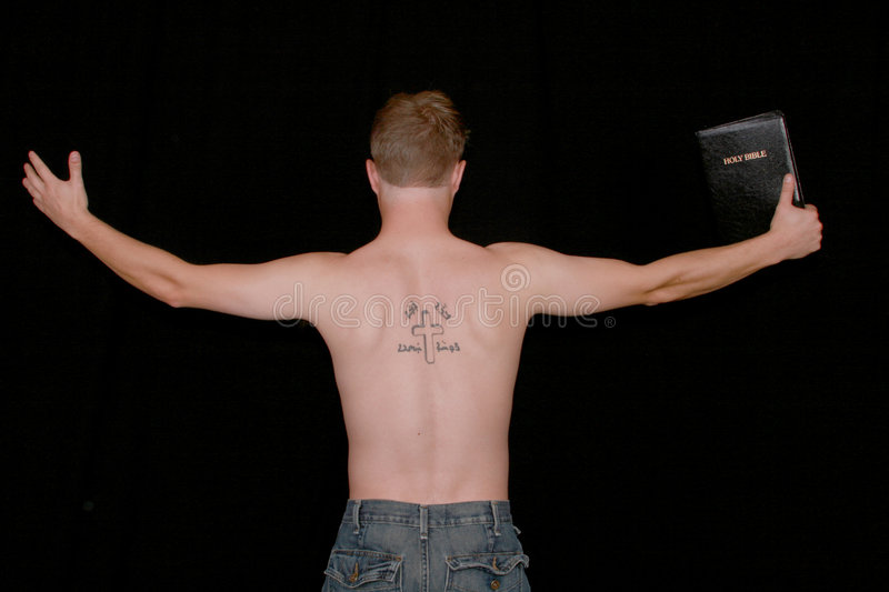 Preaching man. A man preaching with a crucifix and aramiac writing tattooed on his back stock photo
