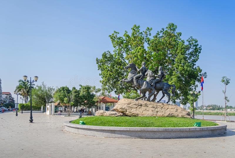 Preah Sisowath Quay con il monumento ai guerrieri Techo Meas e Techo Yot fotografia stock libera da diritti