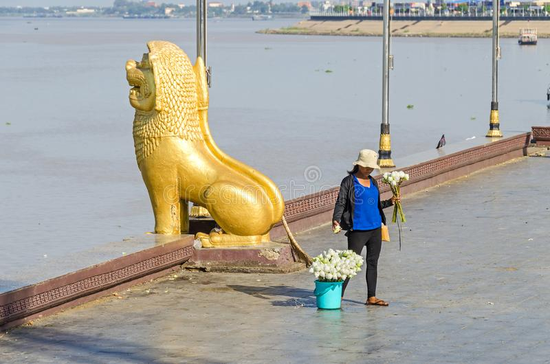 Preah Sisowath Quay en Phnom Penh con la estatua del león del guarda y una mujer que venden las flores de loto fotografía de archivo