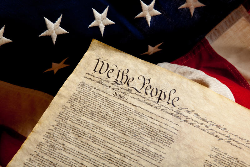 Preample of the constitution and american flag. The preamble of the Constitution of the United States of American on a flag stock photos