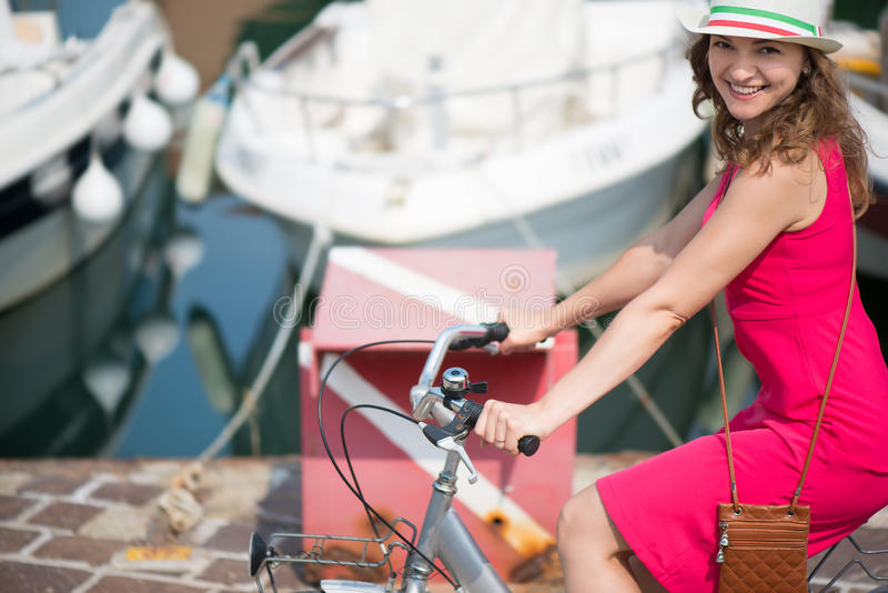 Preaty girl in hat and pink dress riding a bicycle. At Italian streets royalty free stock photo