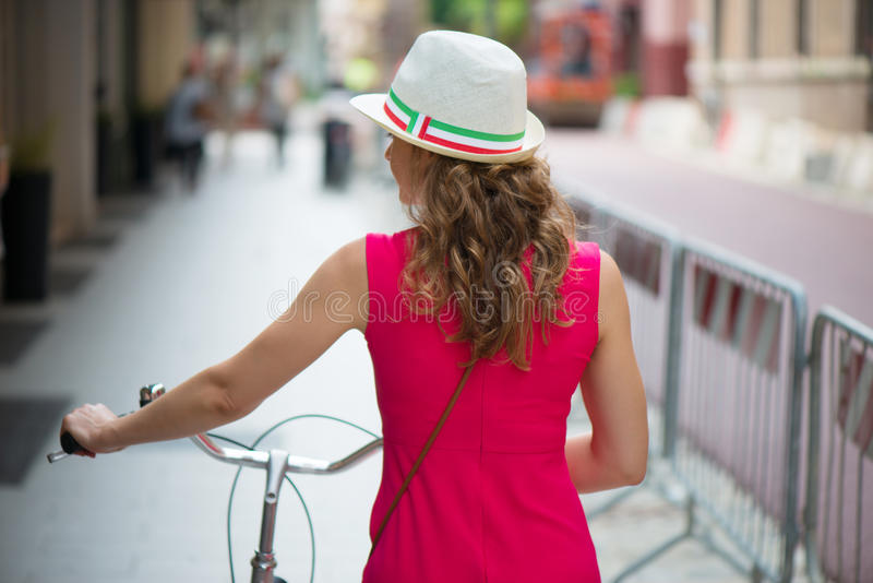Preaty girl in hat and pink dress riding a bicycle. At Italian streets royalty free stock photography