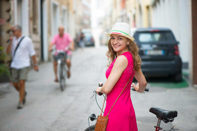 Preaty girl in hat and pink dress riding a bicycle. At Italian streets royalty free stock images