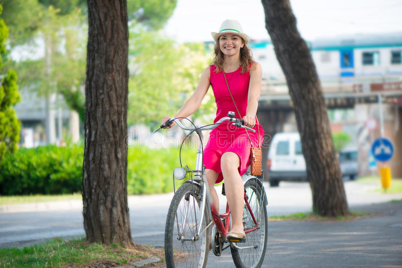 Preaty girl in hat and pink dress riding a bicycle. At Italian streets stock images
