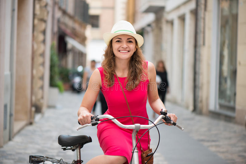 Preaty girl in hat and pink dress riding a bicycle. At Italian streets stock photography