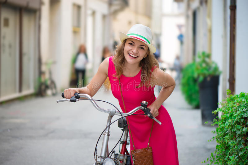 Preaty girl in hat and pink dress riding a bicycle. At Italian streets royalty free stock photos