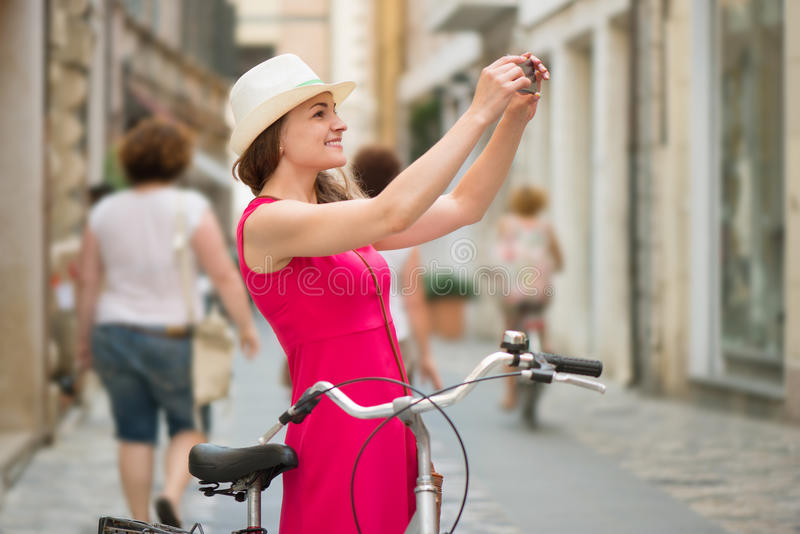 Preaty girl in hat and pink dress riding a bicycle. At Italian streets stock image