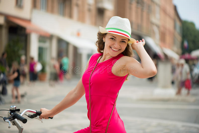Preaty girl in hat and pink dress riding a bicycle. At Italian streets stock photos