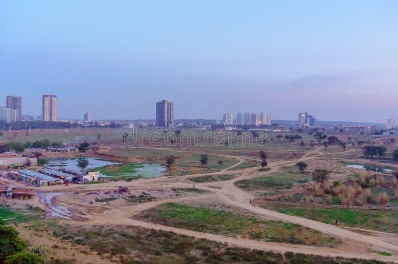 Precários, campos de exploração agrícola vazios com construções altas da elevação no fundo no NCR de Deli do gurgaon imagem de stock