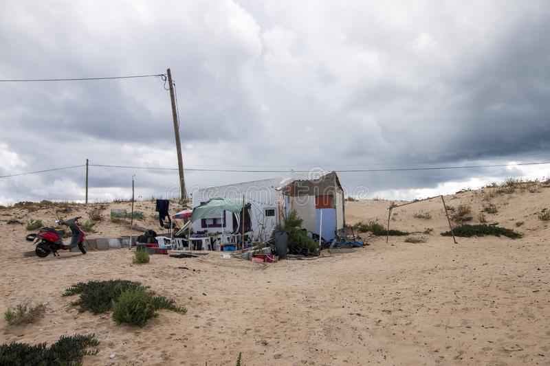 Precarious home at beach. FARO, PORTUGAL: 21th OCTOBER, 2018 - Precarious home with deficient living conditions located in the beach of Faro city, Portugal royalty free stock images