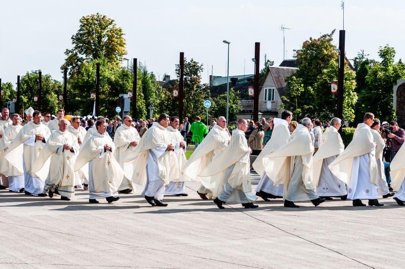 Precedencia de los sacerdotes en el iluvade Å, Lituania septiembre de 2012 fotografía de archivo libre de regalías