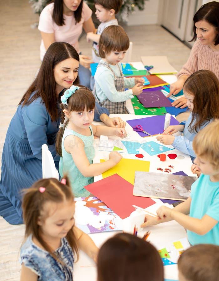 Prechool孩子与纸一起使用在老师的监督下 做项目的小组小孩  免版税图库摄影