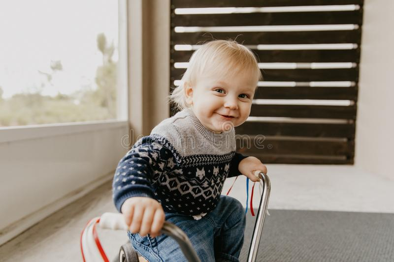 Precious Adorable Cute Little Blonde Baby Toddler Boy Kid Playing Outside on Wooden Toy Bicycle Scooter Mobile Smiling at the Came royalty free stock photography