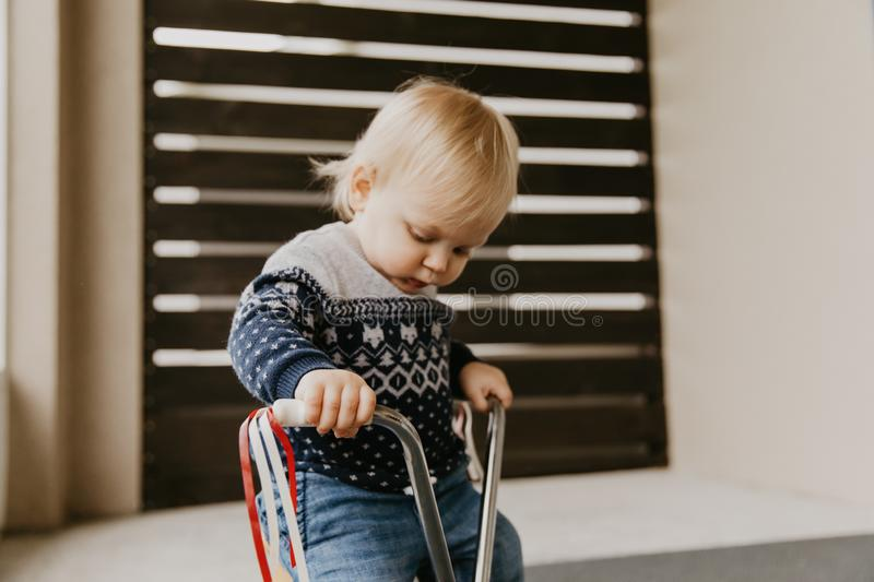 Precious Adorable Cute Little Blonde Baby Toddler Boy Kid Playing Outside on Wooden Toy Bicycle Scooter Mobile Smiling at the Came stock photography