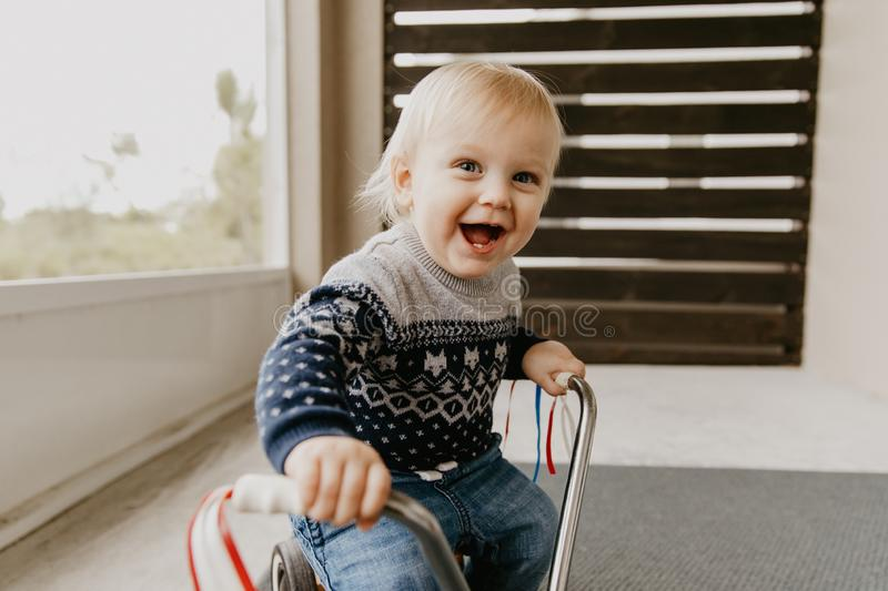Precious Adorable Cute Little Blonde Baby Toddler Boy Kid Playing Outside on Wooden Toy Bicycle Scooter Mobile Smiling at the Came stock image