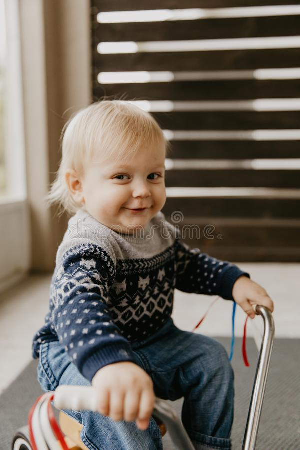 Precious Adorable Cute Little Blonde Baby Toddler Boy Kid Playing Outside on Wooden Toy Bicycle Scooter Mobile Smiling at the Came royalty free stock images