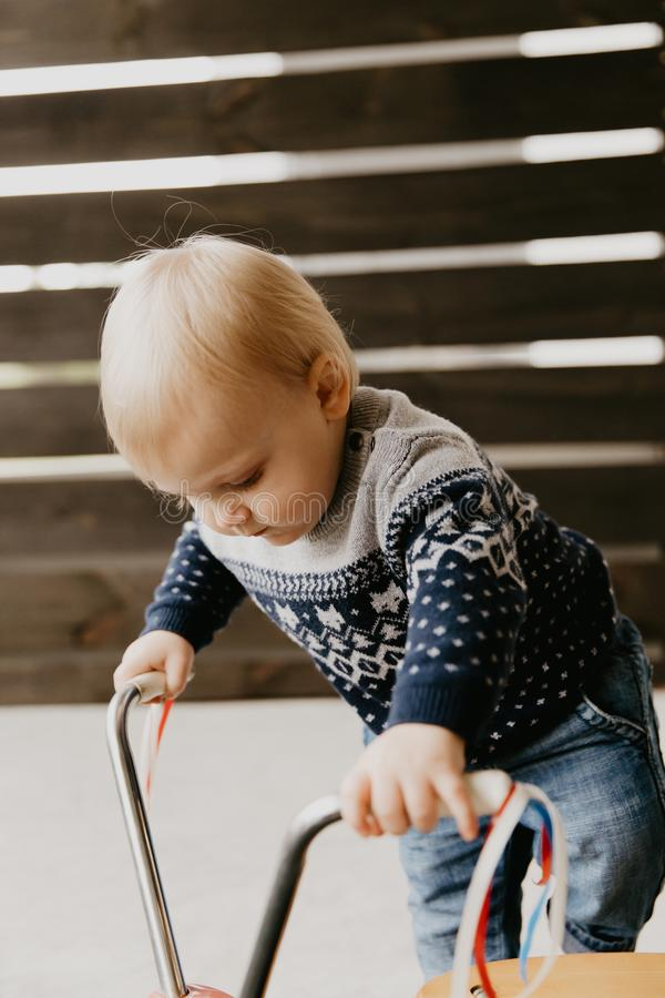 Precious Adorable Cute Little Blonde Baby Toddler Boy Kid Playing Outside on Wooden Toy Bicycle Scooter Mobile Smiling at the Came royalty free stock photos