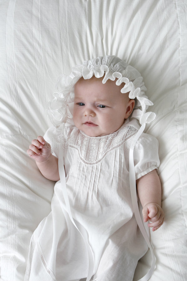 Precious Angel With Bonnet. Three to six month old baby girl in a white dress on a white background. The baby is wearing a white bonnet royalty free stock photo