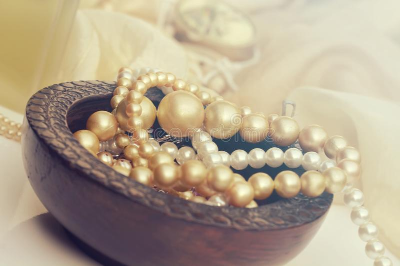 Precious pearl beads in soft light. Beautiful rustic background with golden pearls. Precious pearl beads in soft light royalty free stock image