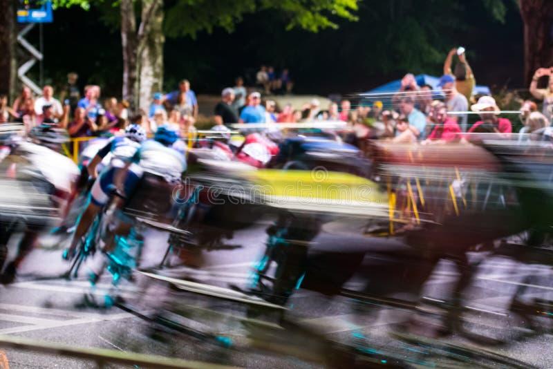 Precipitación de los ciclistas alrededor de la esquina en el crepúsculo imagenes de archivo